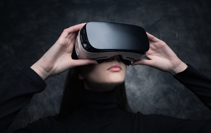 Young beautiful woman wearing a VR headset and experiencing virtual reality