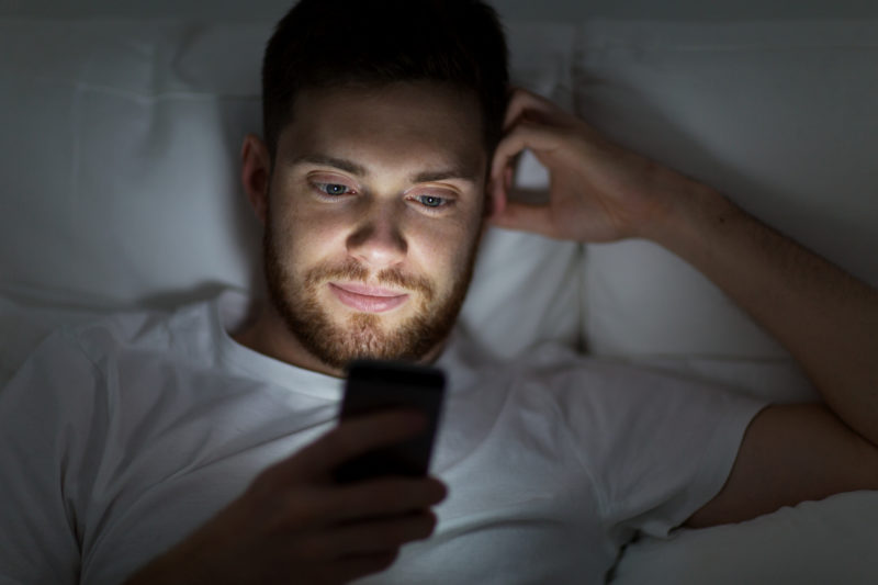 technology, internet, communication and people concept - young man texting on smartphone in bed at home at night
